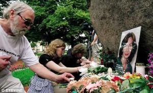 St.Petersburg'da Natalya'nın resmi önünde çiçek bırakan insanlar